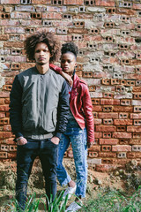 Young black teen couple. Dark skin, mixed race, voluminous african hair, brick wall background