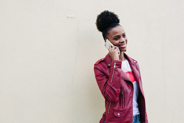 portrait of cheerful black teenage girl with  voluminous African hair, dressed in red Leather Jacket on white background speaking by mobile phone .