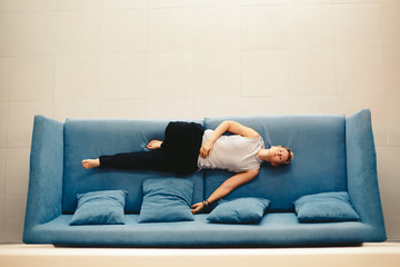 Casual pretty woman wearing short hair lying on blue sofa at home