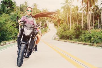 Portrait of female Biker sitting on big motorcycle. Outdoor lifestyle portrait