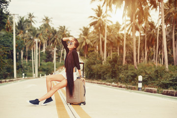 Beautiful style girl seating with suitcase on tropical road