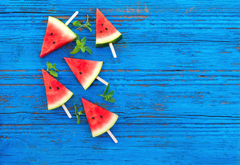 Summer background. Watermelon fruit slice popsicles on a  blue wood background with mint leaves, flat lay.