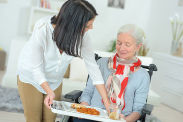 carer serving lunch to senior woman