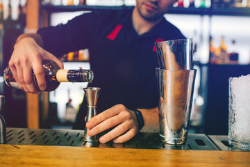 Young barman pouring scotch into the measurable cup. He is preparing an alcohol cocktail. This guy has many botles of alcohol drinks behind him.