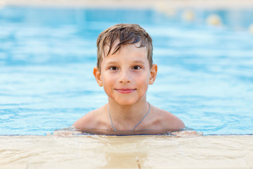 Small boy enjoying swimming in the pool. Children vacation background with copy space