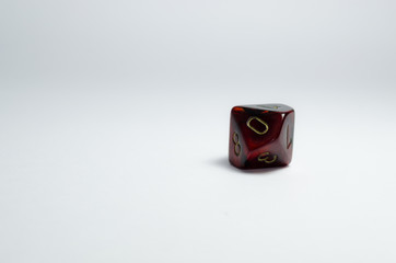 ten-sided dice, red, isolated on a white background with a small shadow. Number zero in focus. Dice of role playing game and dungeons and dragons.