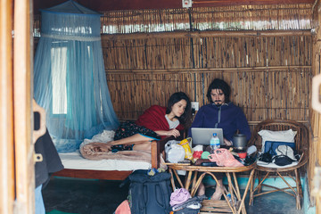 Traveling freelance couple sitting in the bedroom with laptop computer near mosquito net, doing work together