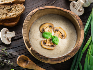 Cream soup with mushrooms on wooden table. Top view.