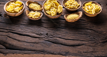 Different pasta types in wooden bowls on the table. Top view.