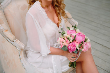 Bouquet of pink peonies and roses in the hands of a girl in a white silk robe