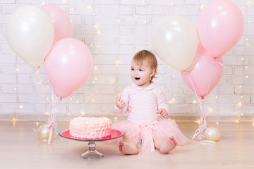 birthday and happiness concept - happy little girl with cake and sweets over brick wall background with lights and balloons