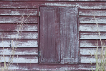Vintage red wooden window on red wood wall with outside wall have dry grass.