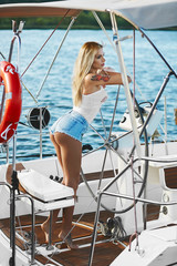 Beautiful fashionable blonde girl in shorts and t-shirt posing on a yacht ship