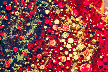 Oil and ink bubbles red and golden drops macro background