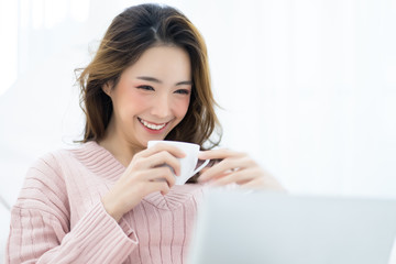 Happy casual beautiful woman working on a laptop sitting on the bed in the house in the winter focus face smile. Winter season and lifestyle Concept.