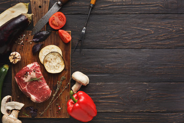 Raw filet mignon steak on wooden board