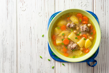 Soup with meatballs, vegetables and chickpea on white wooden table