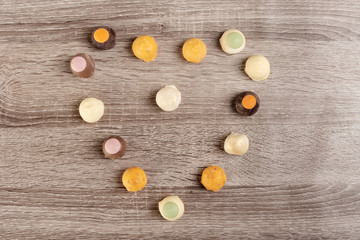 Tasty candies in heart shape for gift on wooden background