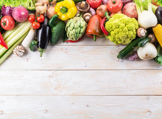 Different colorful vegetables arranged as a frame. Wooden background.