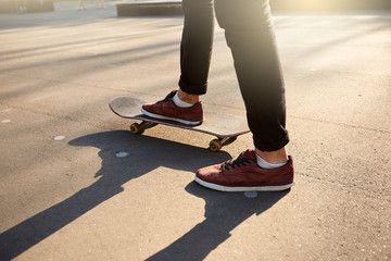 Close-up of skateboarders feet while skating in skate park. Man riding on skateboard. Isolated view, low angle shot.