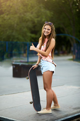 Portrait of fashionable beautiful young woman with a skateboard in a colorful dress in skatepark outdoors