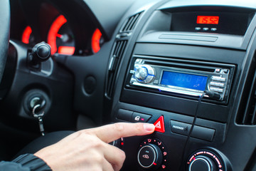 Detail on car dashboard, man finger pressing the emergency lights button while driving.