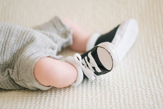 Feet of a newborn baby sneakers, selective focus
