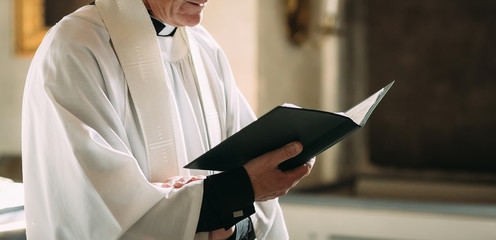 Catholic wedding ceremony. Hands of a priest with the Bible. Copy space
