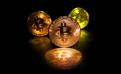Three bitcoin with reflection and blur depth of field on black background, low key