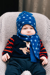 Cute baby sitting and crying in a high chair in blue hat and scarf, swings