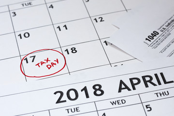 April 17 2018 - Tax Day. Calendar and form 1040 income tax form for 2017 showing tax day for filing