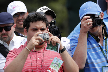 Patrons take pictures during practice for the 2018 Masters golf tournament at Augusta National Golf Club in Augusta