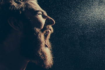 A bearded man angrily screams into a spray of water against a black background. Toned image. Fototapete