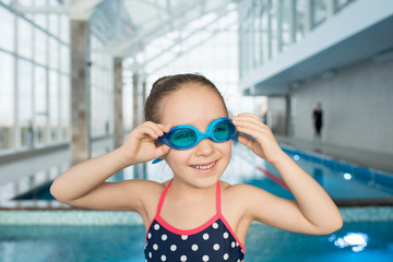 Portrait of cheerful excited beautiful girl adjusting swimming goggles before training in pool