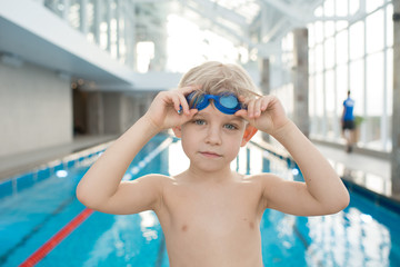 Calm cute boy with blond hair training in swimming pool: he putting on goggles and looking at camera