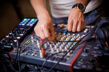 DJ's hands behind the DJ's remote control