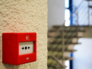 Close-up of the red manual Fire Call Point mounted or installed in the landing on a yellow wall. High-quality macro photography.