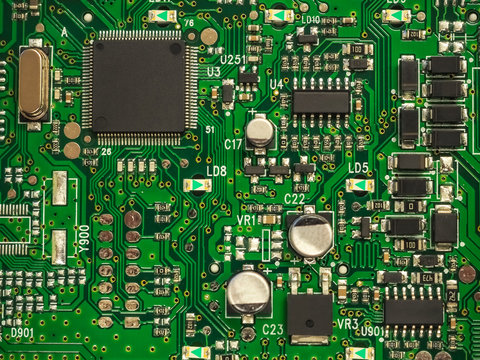 Close-up of electronic circuit board PCB with components: microchip, processor, integrated circuits, capacitors, resistances and electronic connections are noted. High-quality macro photography.