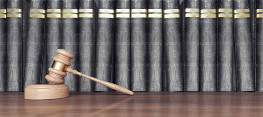Wooden judge hammer on the desk in front of the law books 3D Rendering