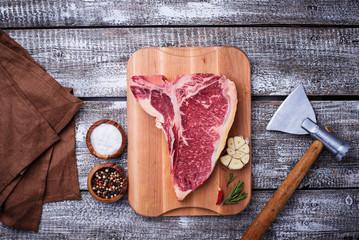 Raw T-bone steak with hatchet