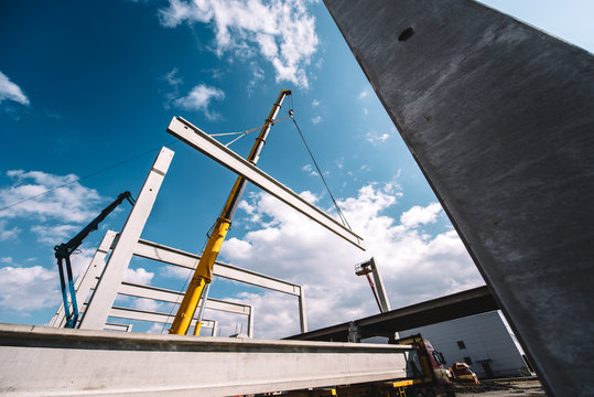 Construction site of prefabricated hall with cement pillars and concrete beams moving crane