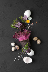 Fresh chicken and quail eggs and watercress on a black background..