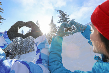 Lovely couple holding hands in shape of heart at snowy resort. Winter vacation