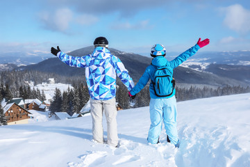 Couple enjoying the beauty of snowy ski resort. Winter vacation