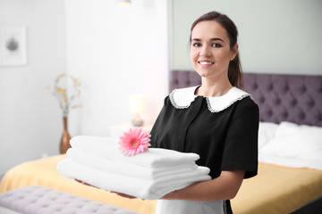 Young maid holding stack of towels and flower in hotel room
