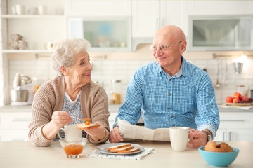 Elderly couple having breakfast in kitchen