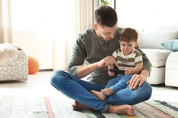 Dad and his son with phone on carpet at home