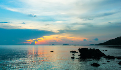 Peaceful sunset reflected on calm sea with silhouettes of rocks in the island of Koh Pha Ngan, Thailand. Relax, paradise destination concept