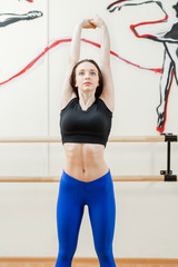 Cute young girl wearing black top and blue pants doing physical exercises warming up. Physical activity concept, stretching exercises. Hall for ballet classes