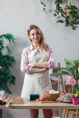 Photo of florist woman in apron at room with flowers